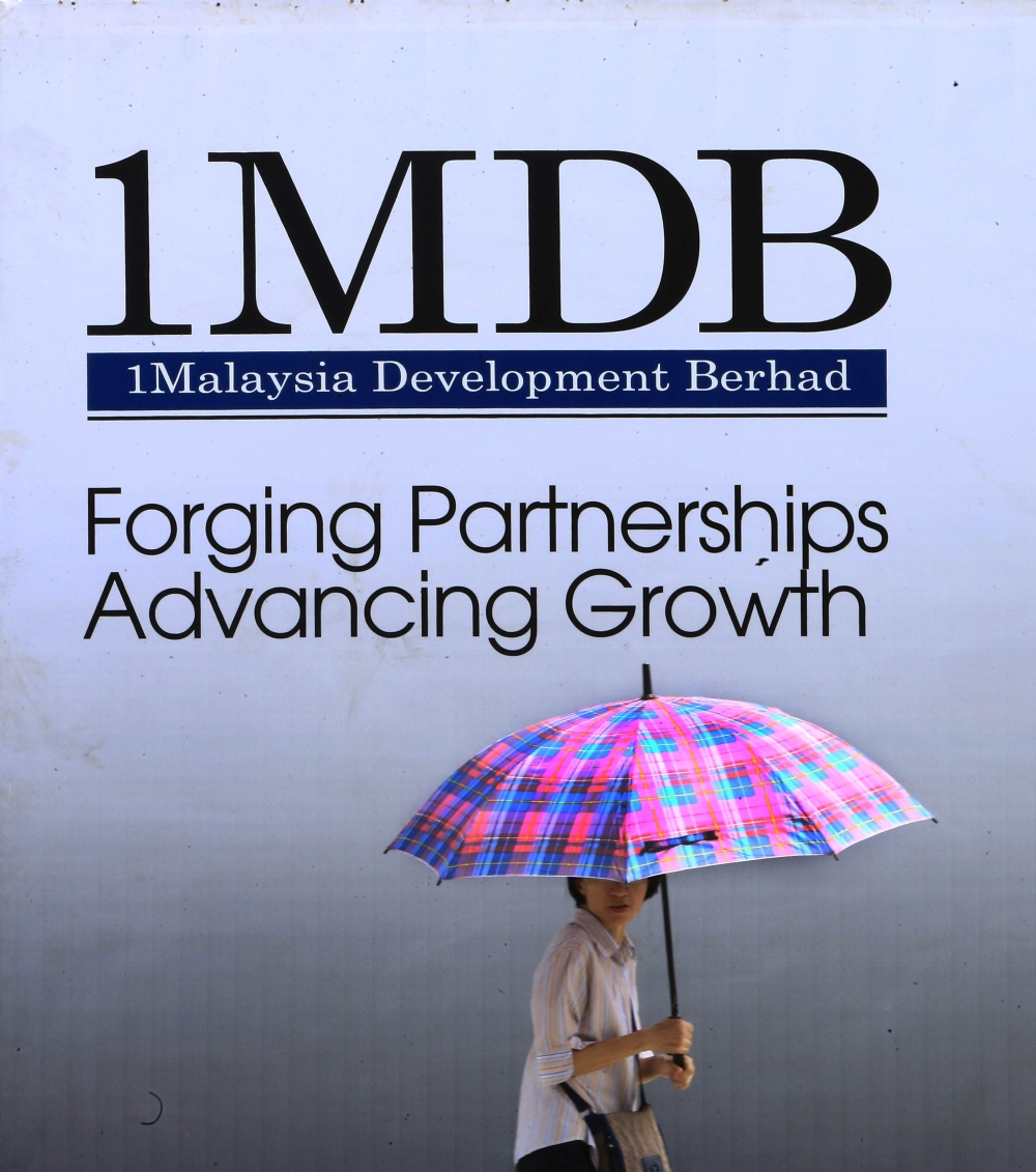 A woman walks past a 1 Malaysia Development Berhad (1MDB) billboard in Kuala Lumpur January 27, 2014. A power plant tender that sovereign wealth fund 1 Malaysia Development Bhd (1MDB) is keen to win before a $2 billion IPO of its power assets has been delayed after bids came in too close to call, government sources said. Picture taken January 27, 2014. REUTERS/Samsul Said (MALAYSIA - Tags: BUSINESS ENERGY)