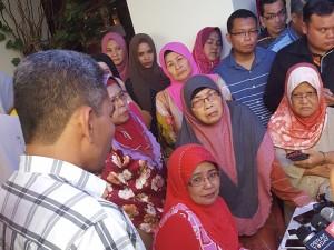 Datuk Hamidah yang bertudung merah, duduk. Gambar asal dari The Malaysian Insider.
