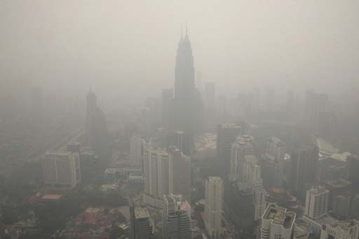 A general view of Malaysia's capital city of Kuala Lumpur is cloaked with the thick hazy skylines at Kuala Lumpur Tower in Malaysia, Friday, June 12, 2009. Malaysian police and airline pilots scoured for fires at swamp forests and garbage dumps Thursday after a decline in air quality signaled the possible return of a seasonal smog. (AP Photo/Lai Seng Sin)