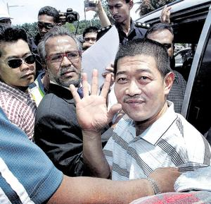 Controversial businessmanTee Yam manages a smile before he was driven off in an unmarked police van. Behind him is his lawyer Datuk Muhammad Shafee Abdullah (in suit).