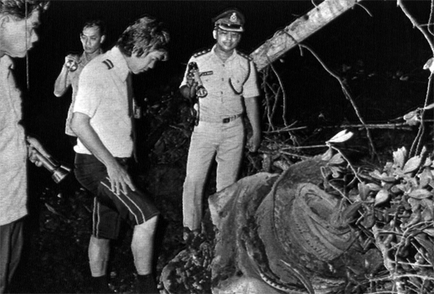 Search teams looking at one of the engines found at the MH653 crash site. Image from NZ Herald