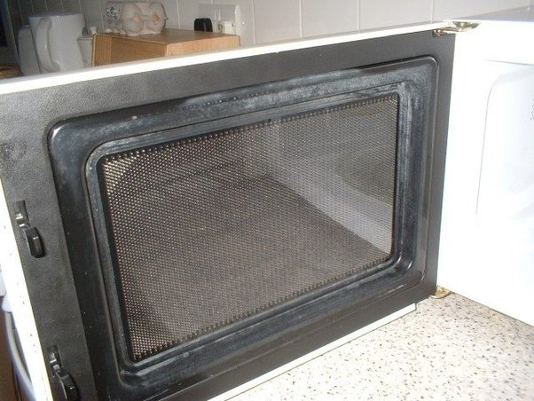 The inside of the glass door prevents the microwaves from affecting your brain. Source