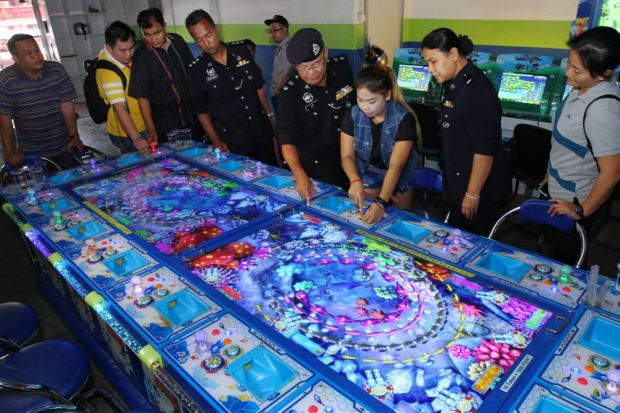 The police looking at a gambling machine. Source