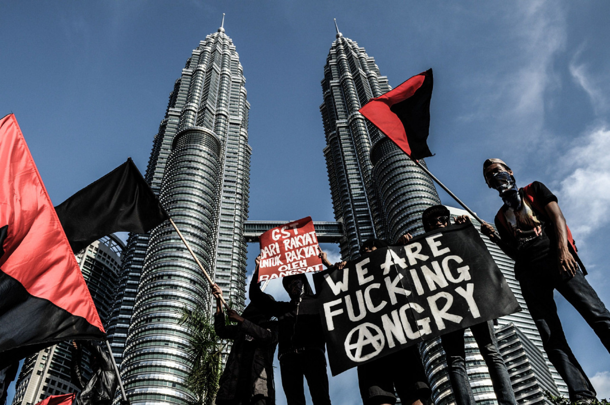 TOPSHOTS TOPSHOTS An Malaysian anarchist group holds placards and their own flags in front of the Malaysia's landmark Petronas Twin Towers during a May Day protest against GST (goods and services tax) in Kuala Lumpur on May 1, 2015. Malaysia's opposition and activists demonstrate on May Day, also known as Labour Day, against the rising cost of living due to reduced subsidies and increased taxes. AFP PHOTO / MOHD RASFANMOHD RASFAN/AFP/Getty Images