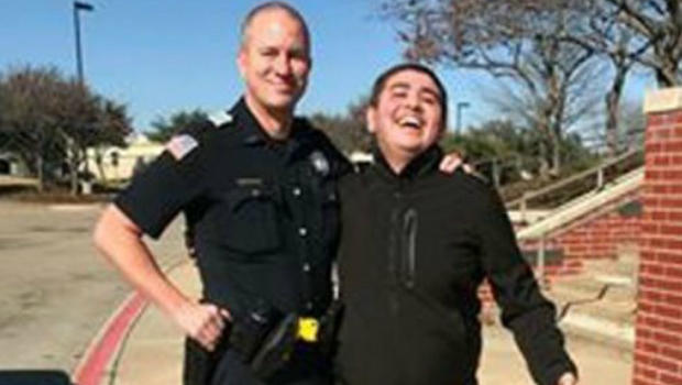 A police officer letting an autistic teen be an officer for a day. Img from CBS News.