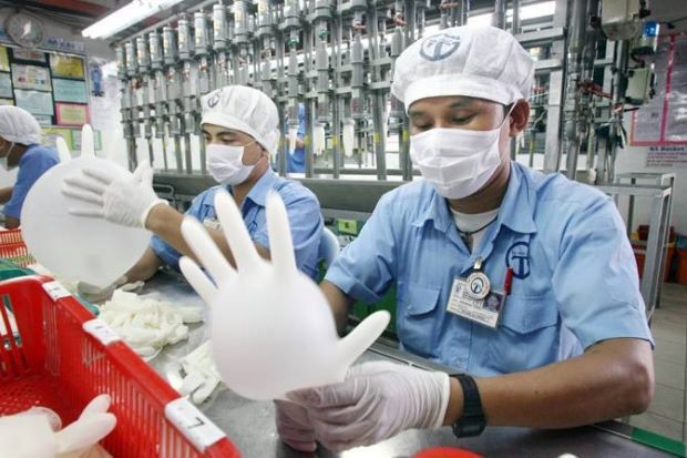 A worker at the Top Glove production line. Image from The Star