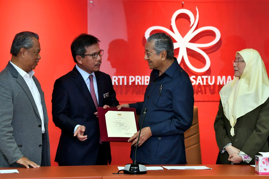 Mahathir receiving the registration certs from ROS. Img from NST.