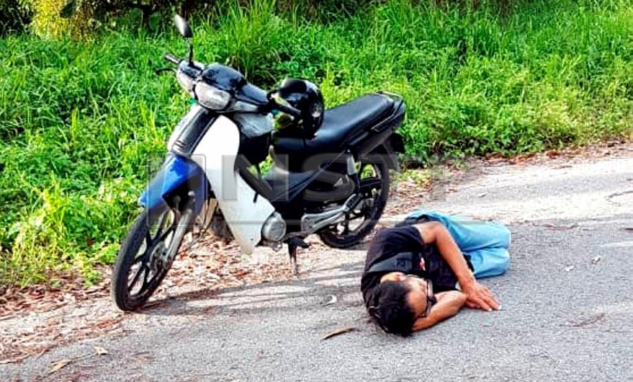 Sleep near your bike? Actually was a drunk guy. Img from Harian Metro.