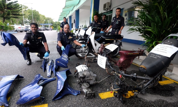 Cops with stolen motorcycle parts. Img from Utusan Online.