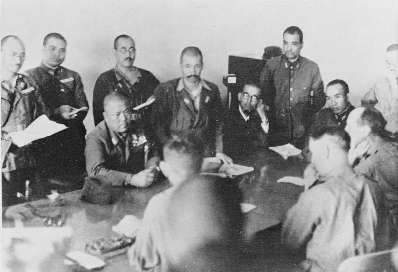 Lt. Gen. Percival (seated between officers) surrenders unconditionally to Lt. Gen. Yamashita in 1942. Image from: Wikipedia