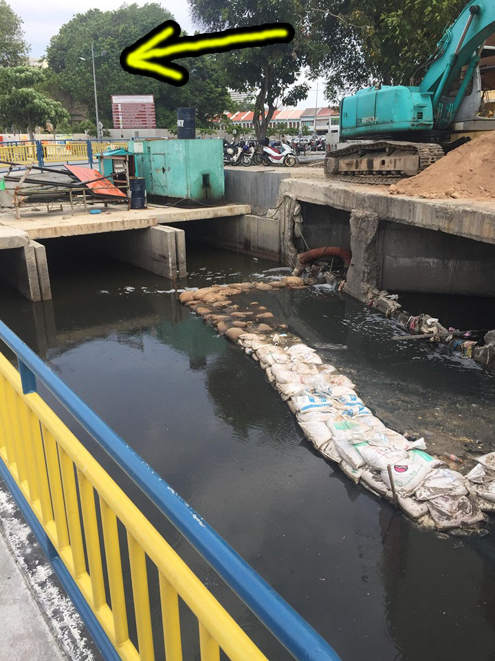 The stormwater drain adjacent to the Sia Boey Market area (indicated with yellow arrows).