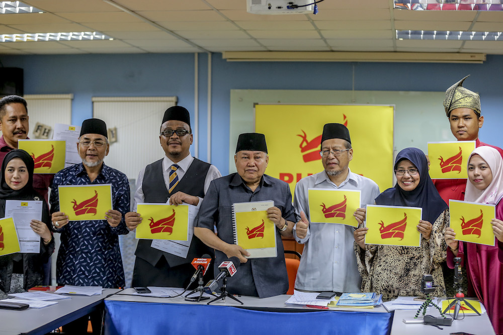 Buzze Azam (second from left) and Ibrahim Ali (third from left) with the party's logo. Img from Malay Mail