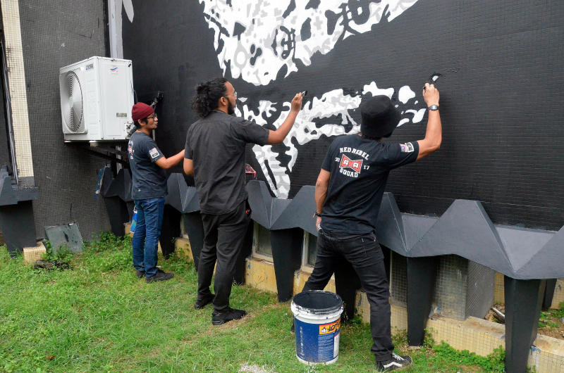 Obi Wang (far left) painting the mural. Img from mStar